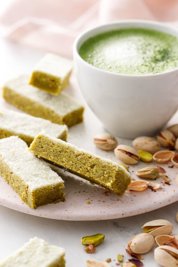 Rectangles of Matcha Pistachio Shortbread with a mug of matcha