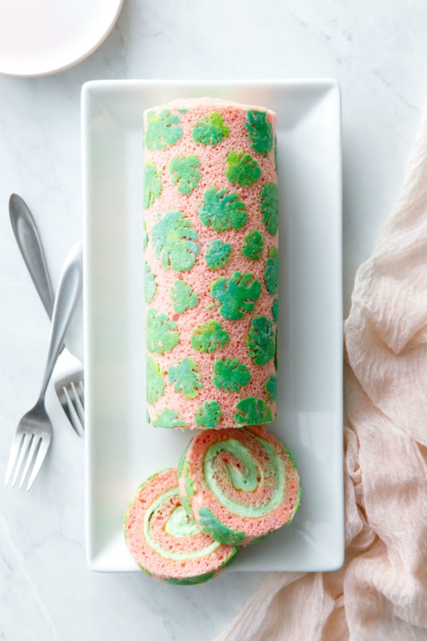Overhead, sliced Monstera Stenciled Cake Roll on white rectangular plate with pink linen