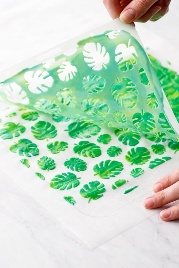 Peeling off the stencil to reveal the monstera leaf design