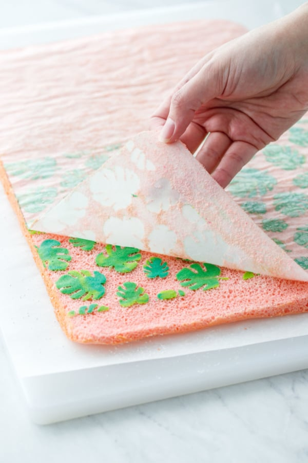 Peeling off the parchment paper to reveal the tropical leaf design
