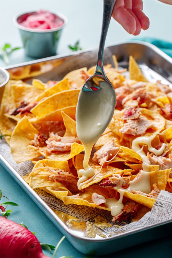 Spoon drizzling nacho cheese sauce over a sheet pan of tortilla chips