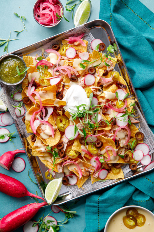 Overhead, sheet pan of Loaded Smoked Chicken Nachos with radishes, micro cilantro on a turquoise background