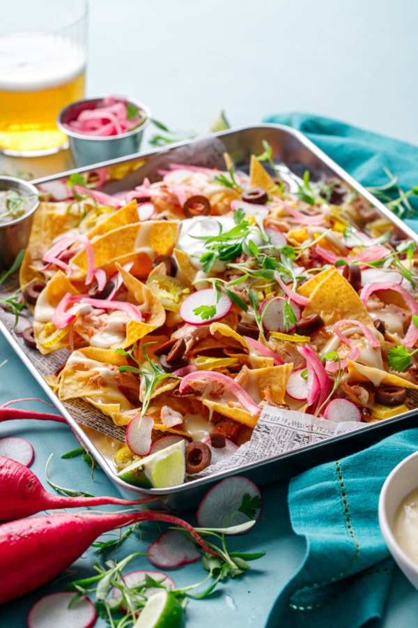 Sheet pan of Loaded Smoked Chicken Nachos with a glass of light beer in the background
