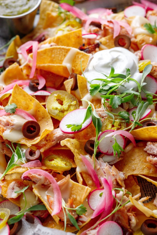 Closeup, Loaded Smoked Chicken Nachos topped with sour cream, cilantro, radishes and pickled onions