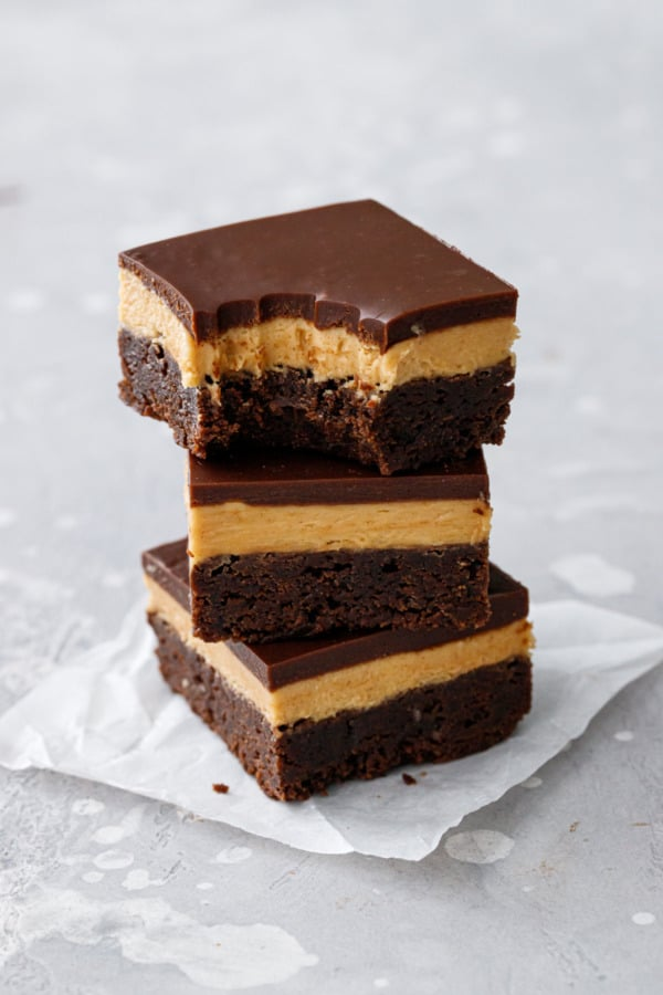 Stack of 3 Milk Chocolate Peanut Butter Ganache Brownies, top one with a bite out of it