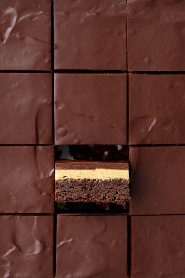 Overheat, sliced squares of Milk Chocolate Peanut Butter Ganache Brownies, one brownie tilted on its side to show the layers