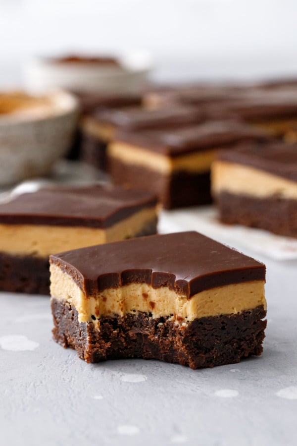 Bite of Milk Chocolate Peanut Butter Ganache Brownies, showing the three distinct layers