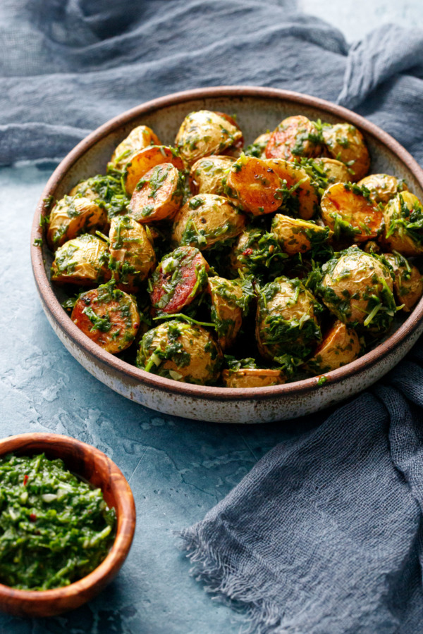 Shallow bowl with small halved roasted potatoes tossed with a green arugula chimichurri, small bowl on the side