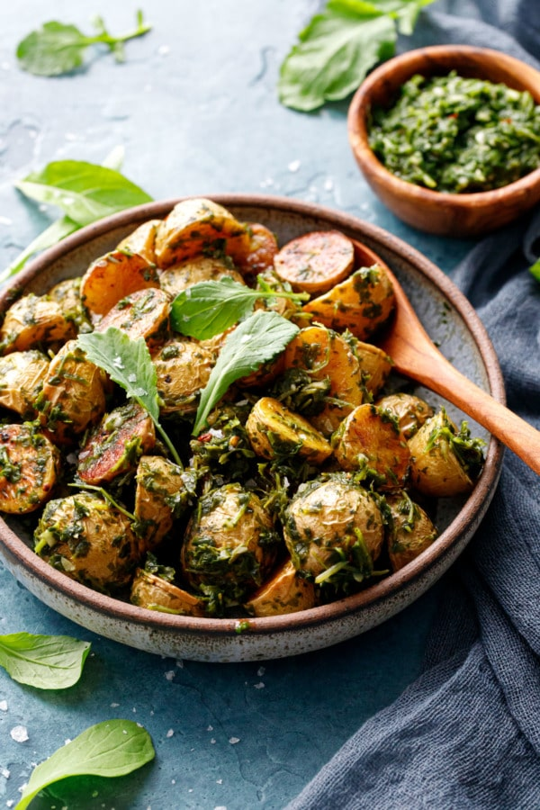 Shallow bowl filled with roasted potatoes tossed with arugula chimichurri, small baby arugula leaves scattered on top