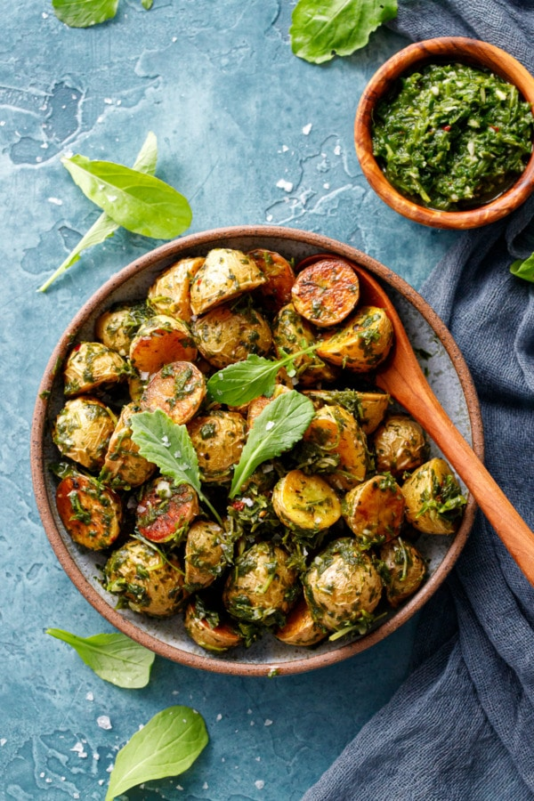 Ceramic bowl with halved baby potatoes, roasted until golden and tossed with arugula chimichurri sauce, small bowl on the side