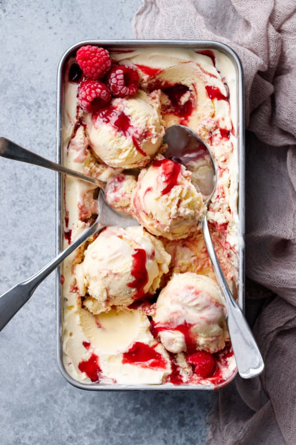 Overhead, silver loaf pan with Toast & Jam Ice Cream, messy scoops and multiple spoons.