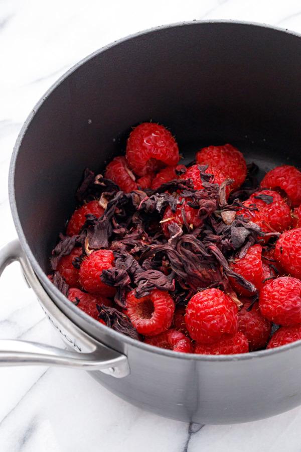 Saucepan with fresh raspberries and dried hibiscus flowers.