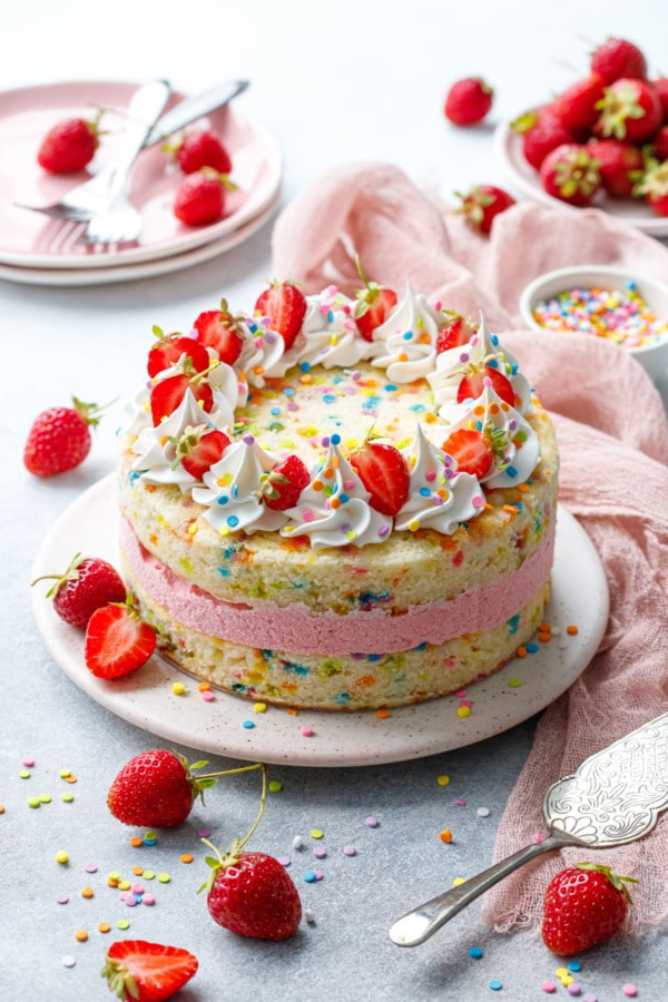 Strawberry Funfetti Ice Cream Cake on gray with pink linen and fresh berries