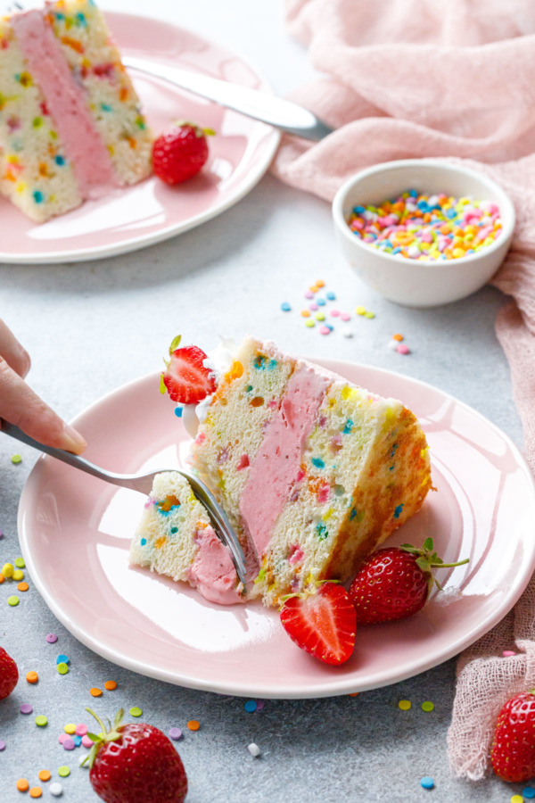Fork cutting a piece out of a slice of Strawberry Funfetti Ice Cream Cake