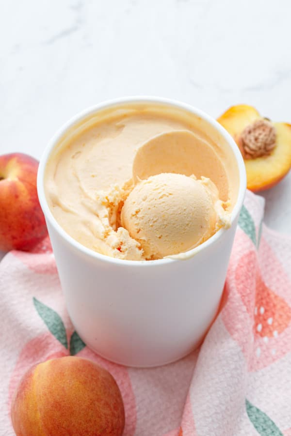 White container with peach ice cream and one scoop, sitting on a peach-graphic towel with fresh peaches