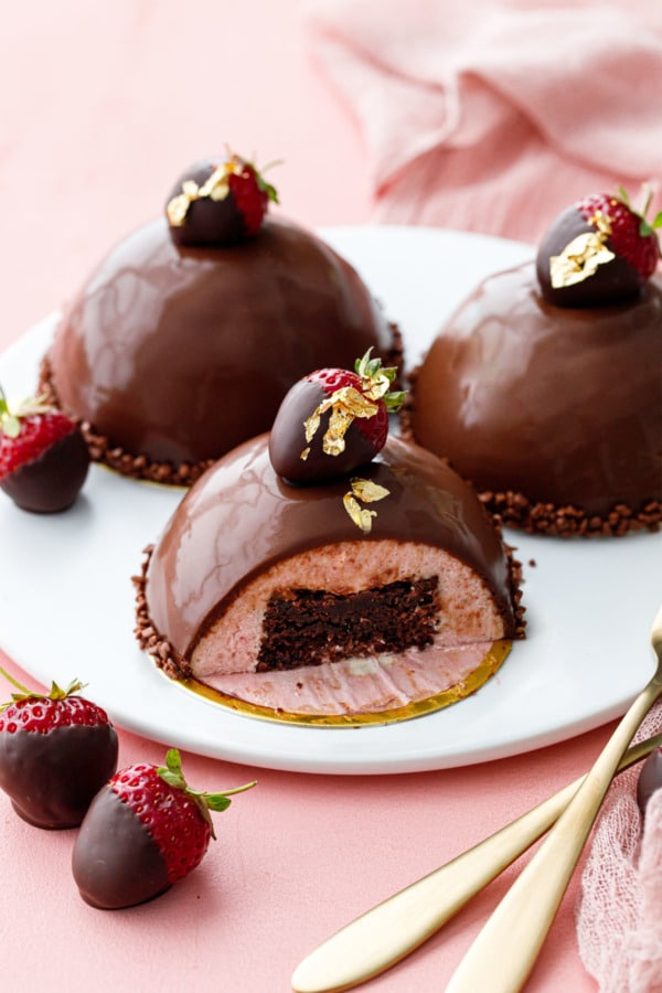 Strawberry mousse cakes covered in chocolate ganace, three on a white plate, one sliced to show the brownie inside
