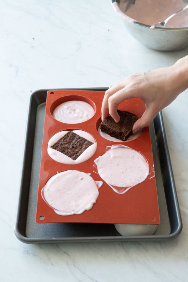 Placing the square of brownie in the mousse-filled silicone molds