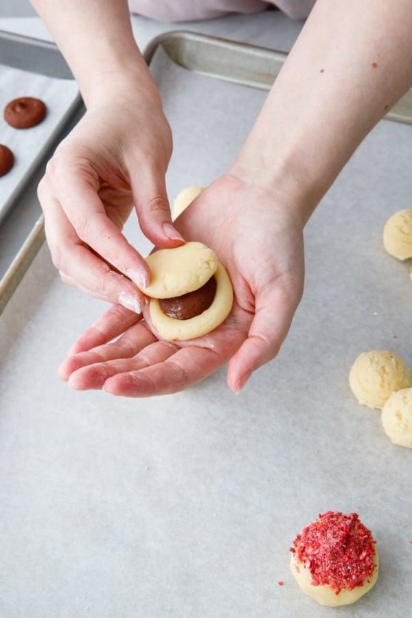 Pressing two pieces of dough around the frozen chocolate ganache center
