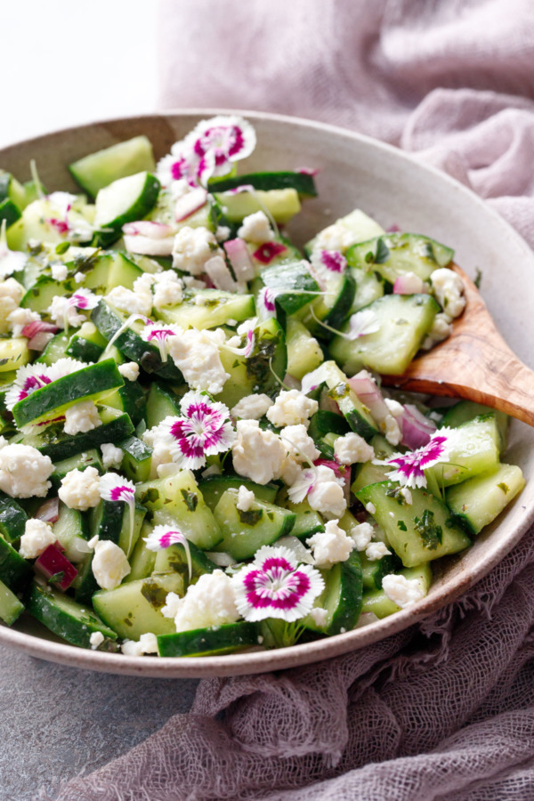 Cucumber & Feta Salad with Herb Vinaigrette and garnished with edible flowers, in bowl with wooden spoon