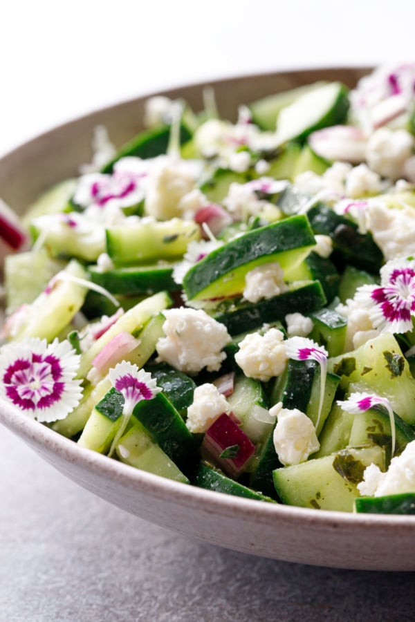 Closeup of Cucumber & Feta Salad with purple and white edible flowers