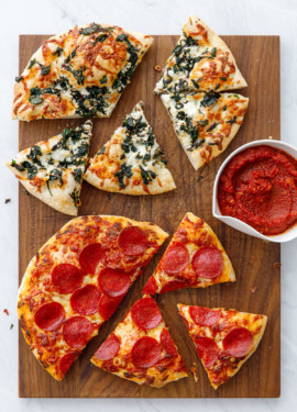 Overhead wooden cutting board with two sliced pizzas (pepperoni and pizza bianca), with a bowl of sauce