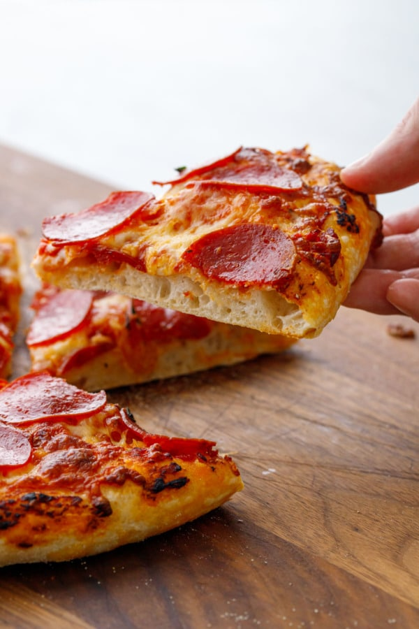 Closeup of sliced piece of pepperoni pizza to show texture of curst