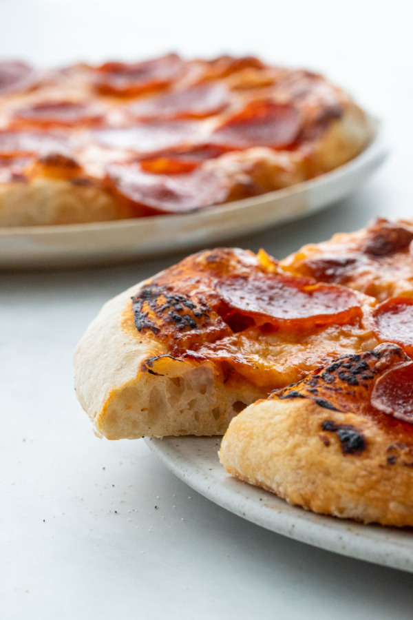 Side view, pepperoni pizza with one slice cut out to show the texture of the crust.