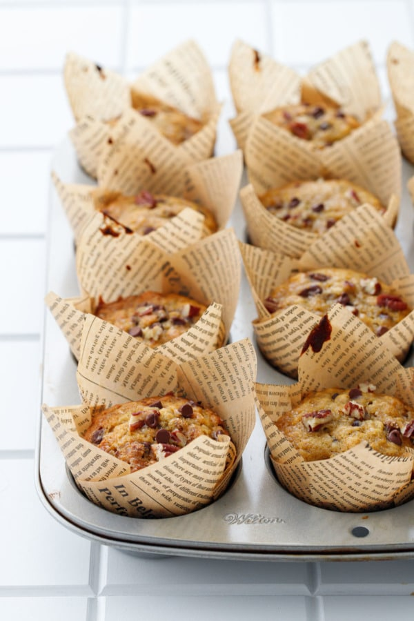 Silver muffin tin with newsprint tulip wrappers, baked banana bread muffins on a white background
