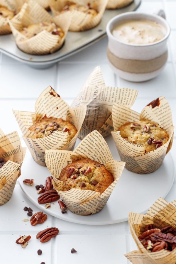 White tile background with banana bread muffins in tulip papers, cup of coffee and muffin tin in the background