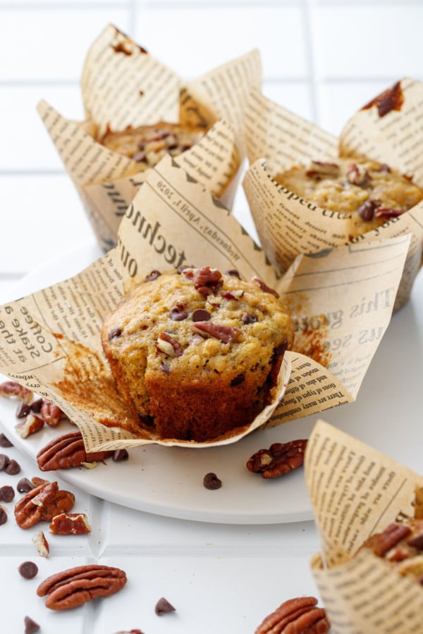 White plate with three banana bread muffins, one wrapper peeled off to show the browned edges of the muffin