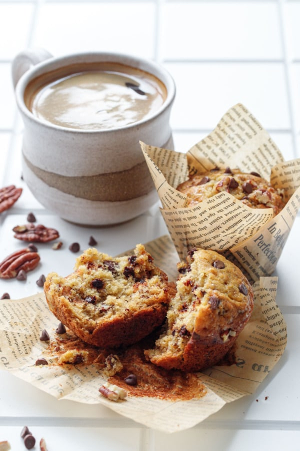 Chocolate chip banana bread muffins, one split in half to show texture, with a cup of coffee in homemade ceramic mug