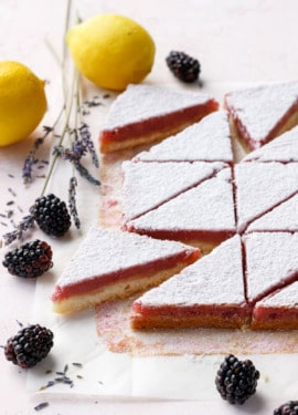 Blackberry Lavender Lemon Bars cut into triangles and dusted with sugar