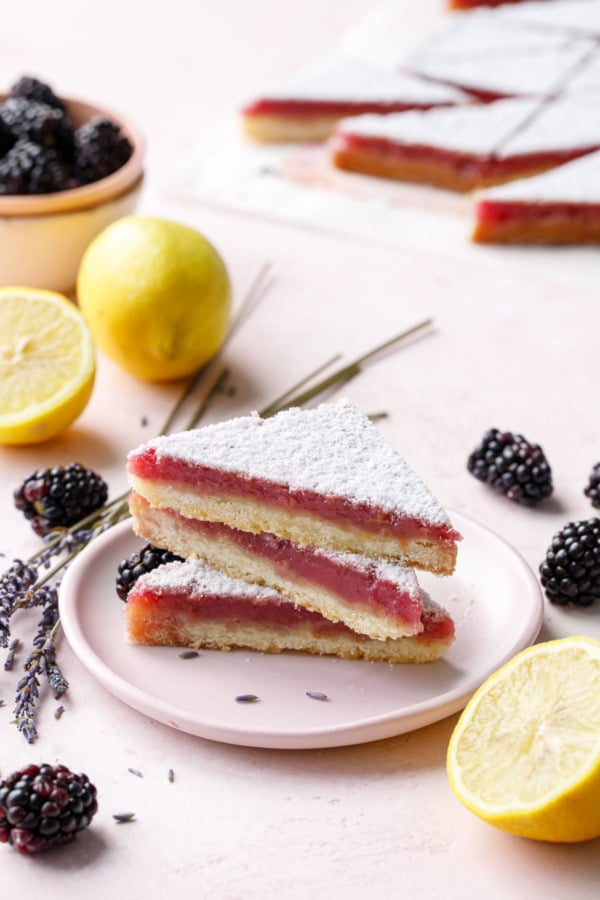 Stack of three triangle shaped Blackberry Lavender Lemon Bars on a pink plate