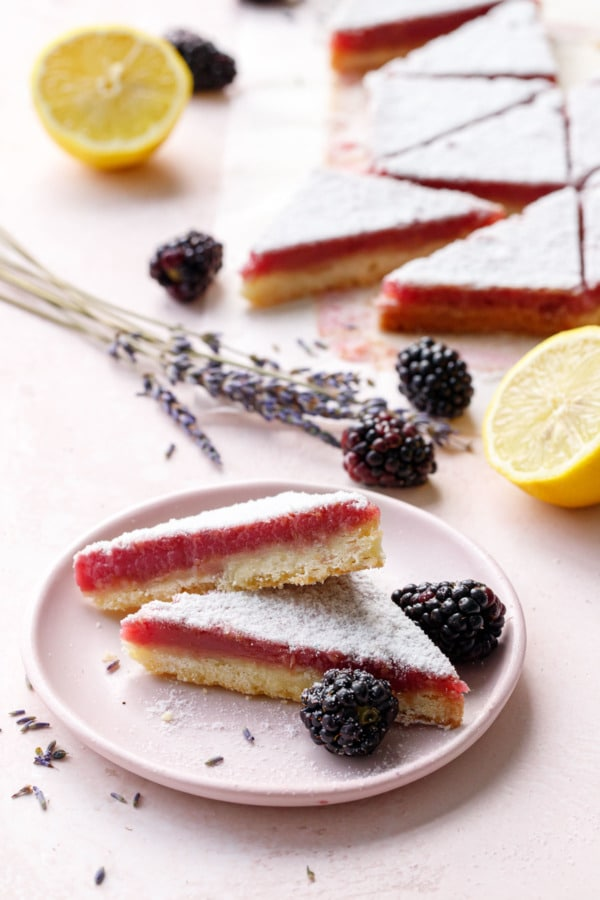 Stack of three Blackberry Lavender Lemon Bars cut into triangles on a pink plate
