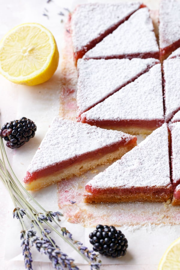 Blackberry Lavender Lemon Bars cut into triangles, defined layers of yellow shortbread and pink topping with powdered sugar
