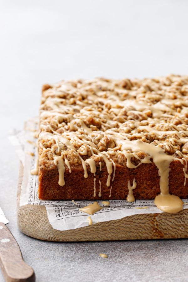 Wood board with Espresso Crumb Coffee Cake, drizzled with coffee glaze dripping down the sides and newsprint parchment paper