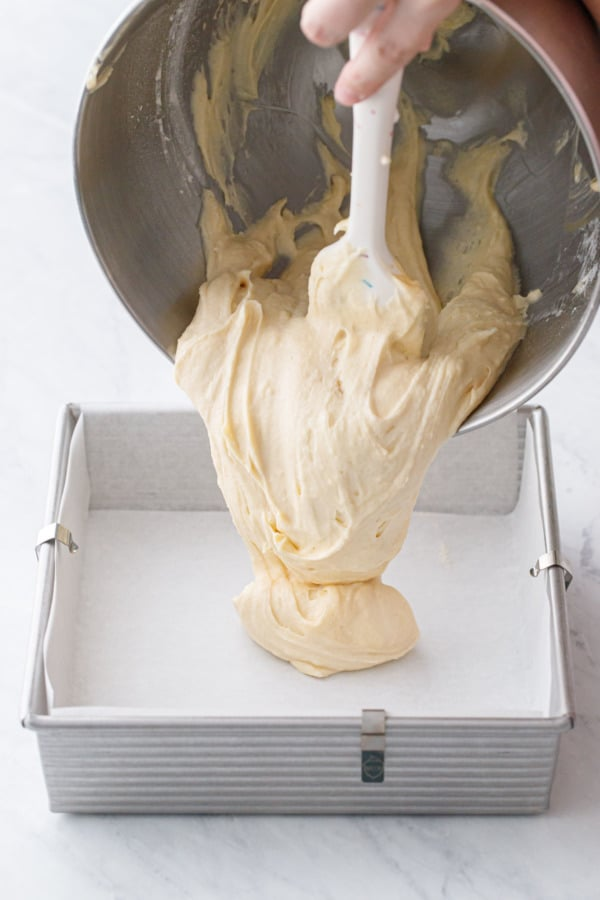 Pouring coffee cake batter into a parchment-lined baking pan