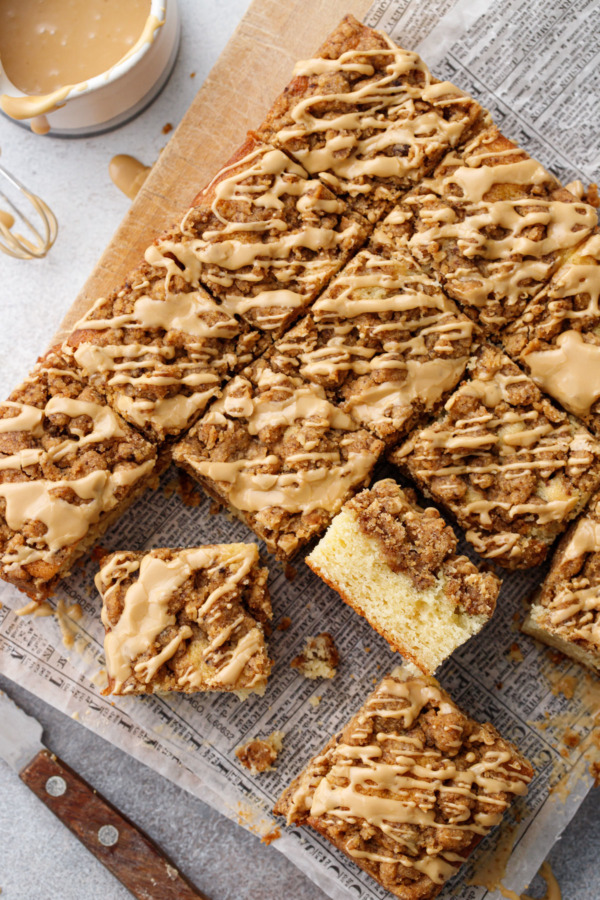 Overhead, offset grid of coffee cake squares, on a wood board with creamer filled with glaze and wooden-handled knife