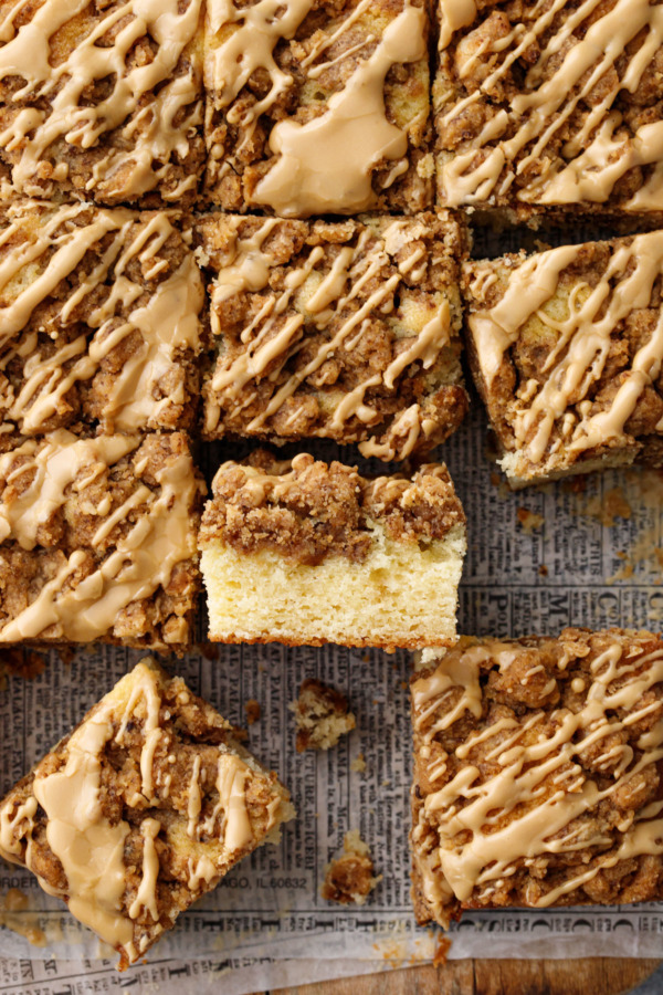 Overhead, grid of cut squares of coffee cake, one on its side to show the cake and crumb layers