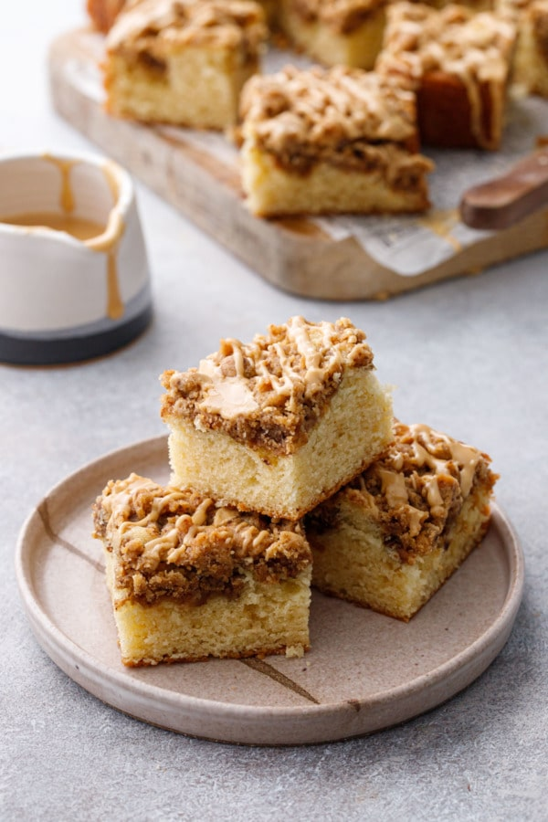 Ceramic plate with pyramid stack of coffee cake squares, wooden cutting board with more slices and cup of glaze in the background
