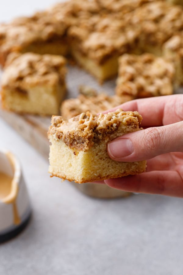Hand holding a slice of Espresso Crumb Coffee Cake, cutting board with more pieces in the background
