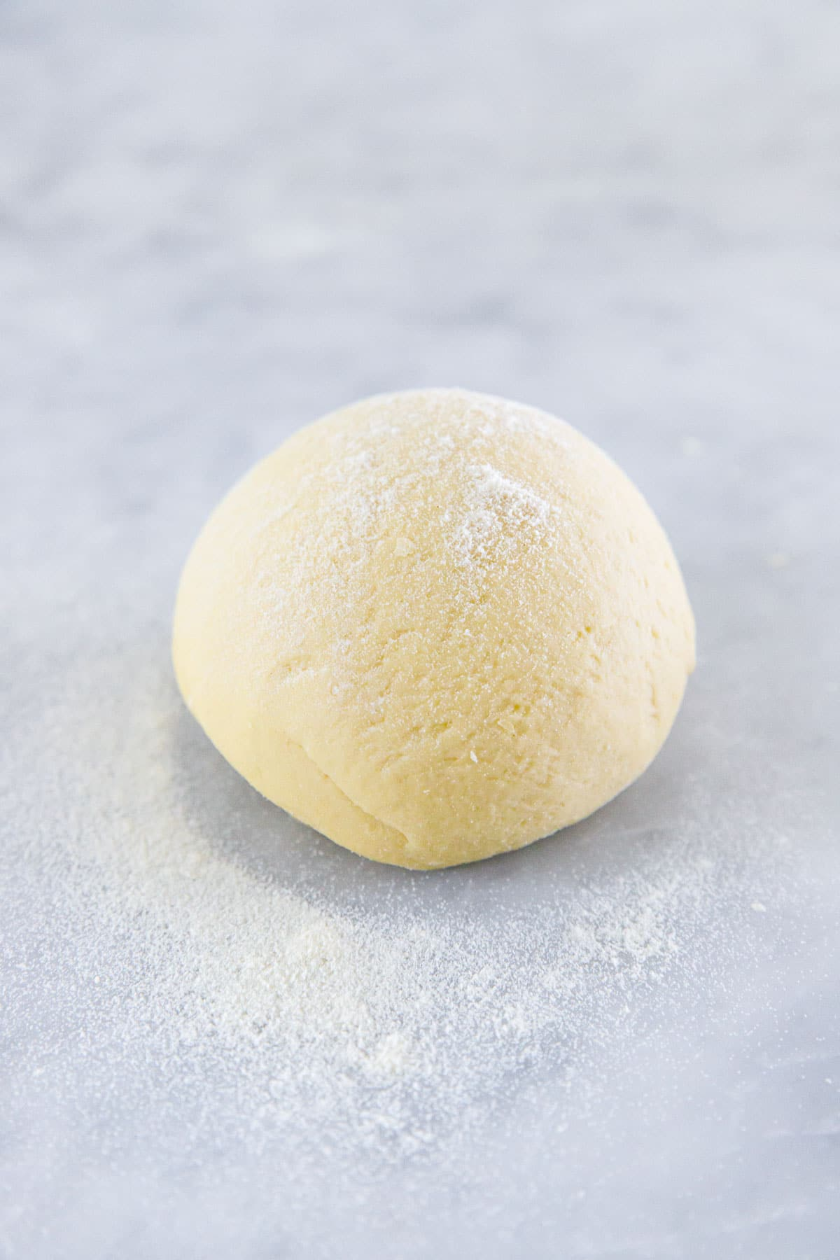 Freshly kneaded ball of homemade sourdough pasta dough, dusted with semolina on a marble surface.