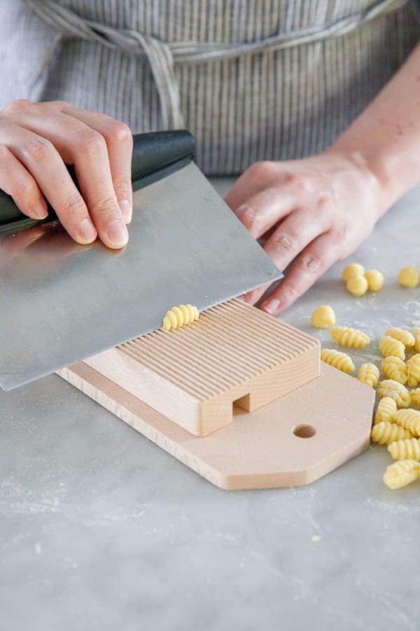 Shaping gnochetti sardi pasta, using a bench scraper and a gnocchi board.