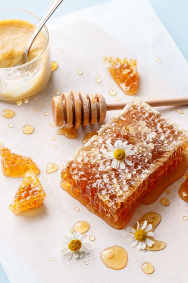 Parchment surface with piece of honeycomb, chamomile flowers, and a wooden honey drizzler