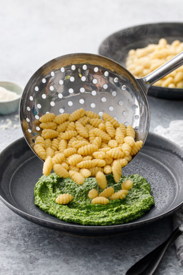 Metal strainer pouring freshly cooked gnochetti sardi into a bowl spread with pesto sauce
