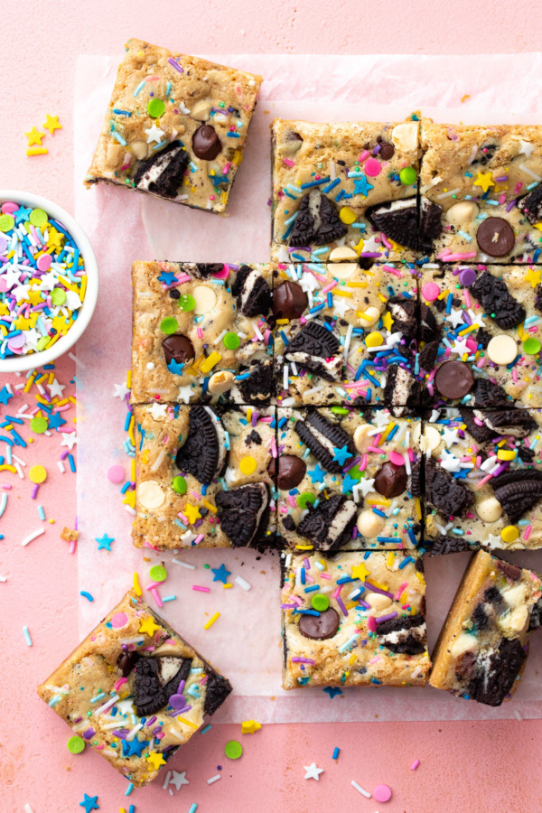 Overhead, squares of sprinkle cookie party blondies on a pink background, with bowl of sprinkles on the side