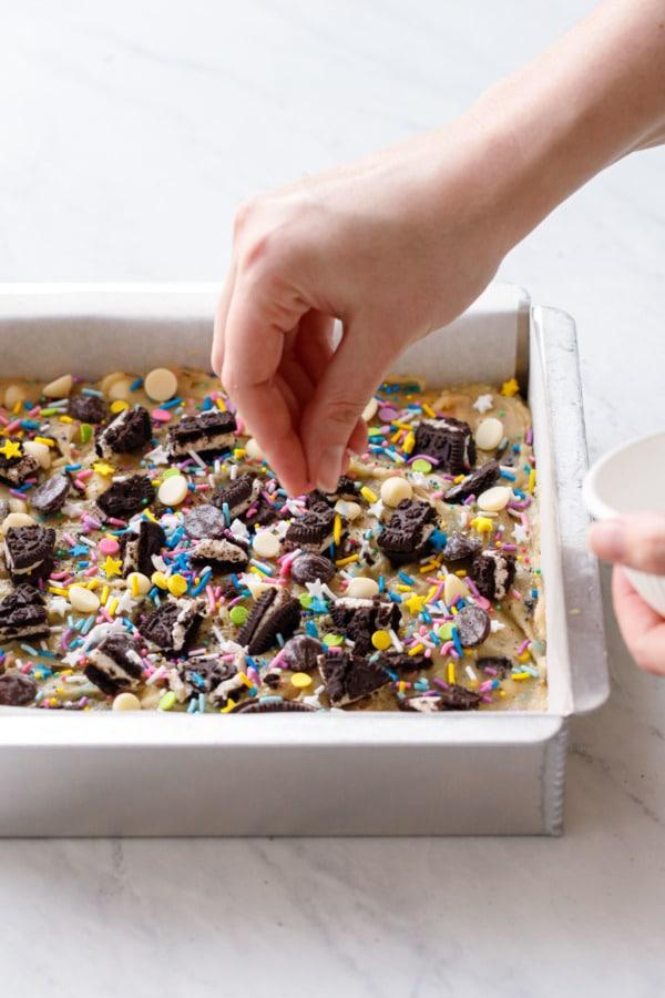 Sprinkling more colorful sprinkles on top of the blondies before baking