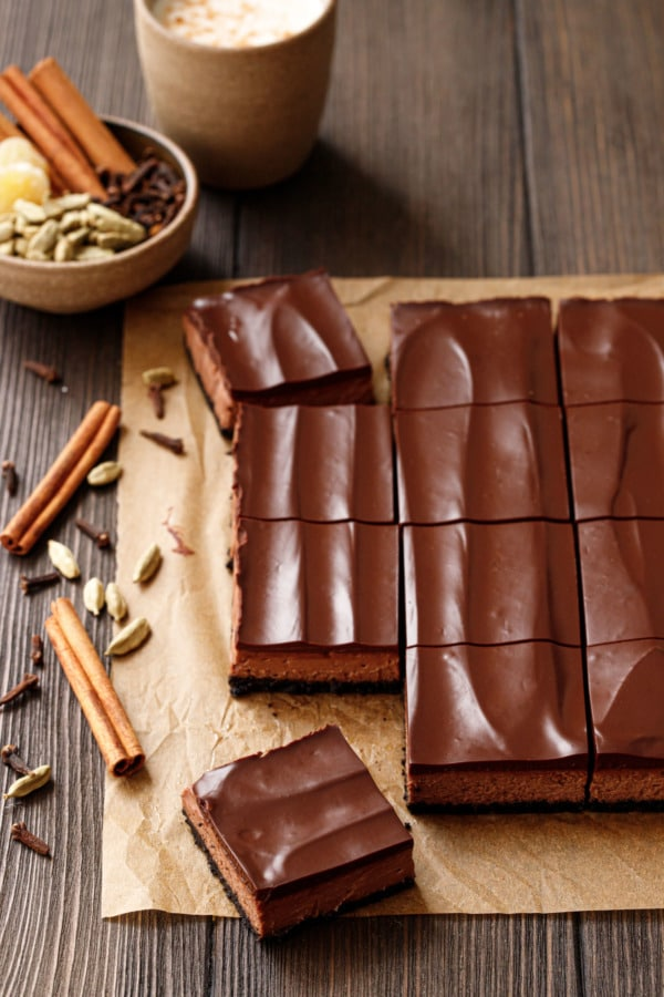 Chocolate Chai Cheesecake Bars cut into squares, on natural parchment and a wood background