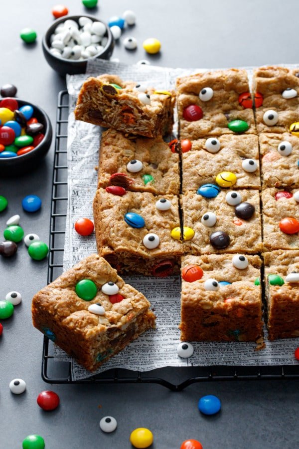 Monster Cookie Bars, topped with M&Ms and candy eyeballs cut into squares on a dark background