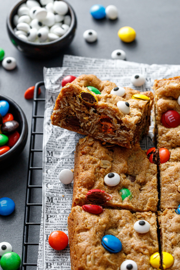 Cut square of Monster Cookie Bar, tilted to show the texture of the oats and candy pieces inside.